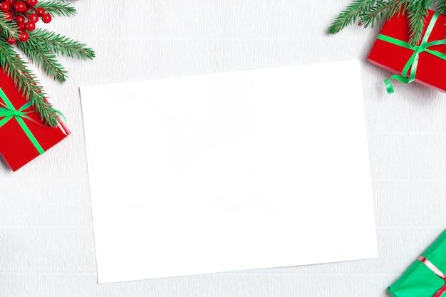 Lettera vuota vuota di natale a babbo natale. mockup di natale. decorazioni natalizie, pigne, rami di abete su sfondo bianco. appartamento laico, vista dall'alto, copia dello spazio.