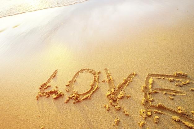 Lettere d'amore scritte a mano in sabbia sulla spiaggia