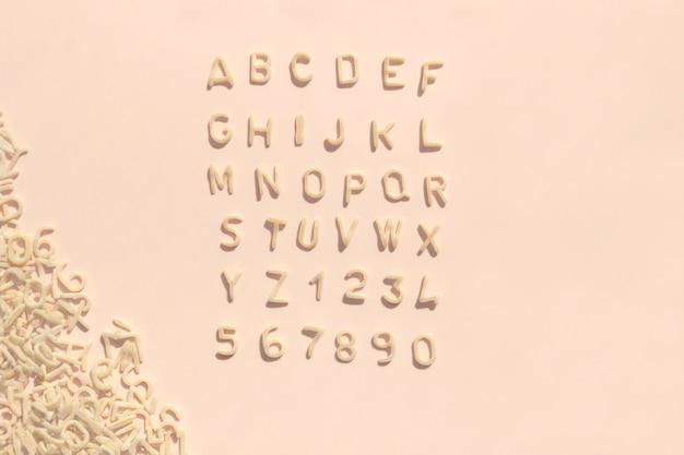 Lettere dell'alfabeto di pasta per cibo per bambini su sfondo rosa chiaro. colore pastello per i pasti dei bambini.