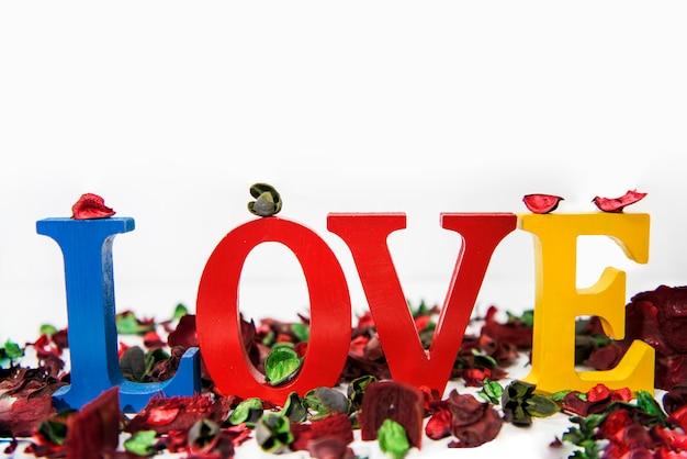 Lettere di legno colorate amore su fondo bianco.