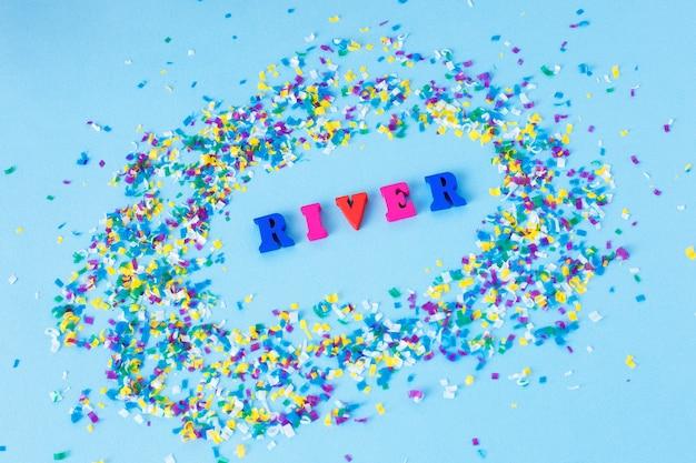 Lettere di legno con la parola fiume intorno a particelle microplastiche su sfondo blu.