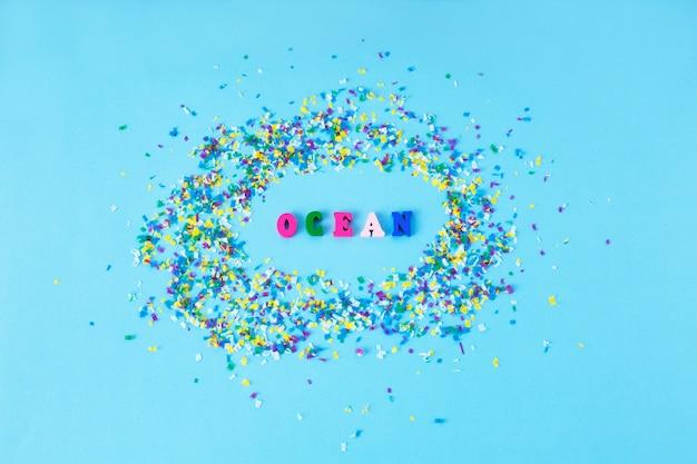 Lettere di legno con la parola ocean intorno a piccole particelle di plastica su uno sfondo blu.