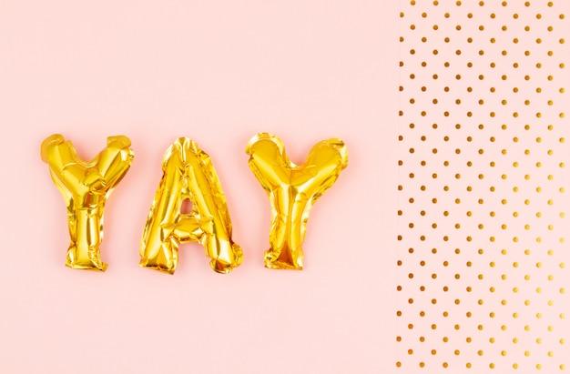 Lettere gonfiate yay ove lo sfondo pastello con pois dorati. festa, celebrazione, vacanze