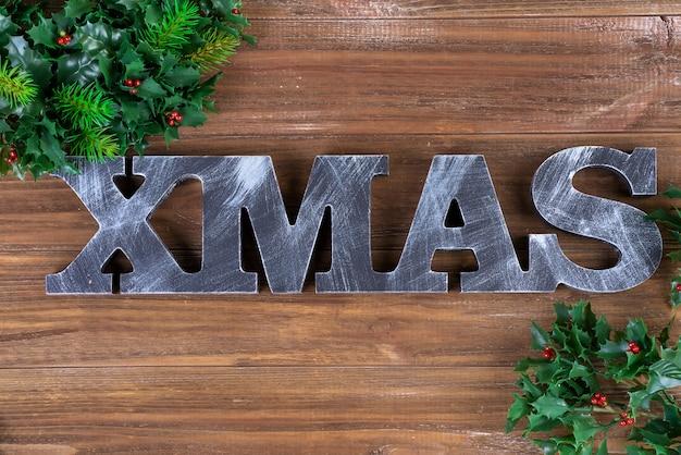 Lettere in legno di natale con rami in forma su uno sfondo di legno. biglietto natalizio. disteso