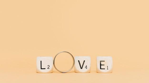 Lettere in legno e anello di fidanzamento ortografia amore sullo sfondo beige