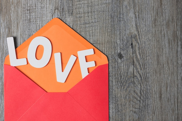 Lettere in legno poste su una busta rossa e poste su un tavolo di legno grigio