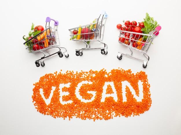 Lettering vegano con deliziose verdure in piccoli carrelli della spesa