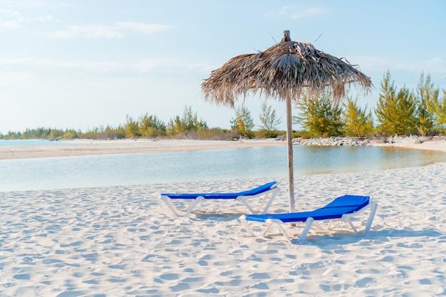 Lettini ed ombrellone sulla spiaggia bianca