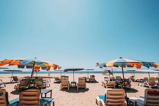 Lettini sulla spiaggia tropicale con cielo calmo. vista mare e spiaggia di sabbia, sfondo estivo.