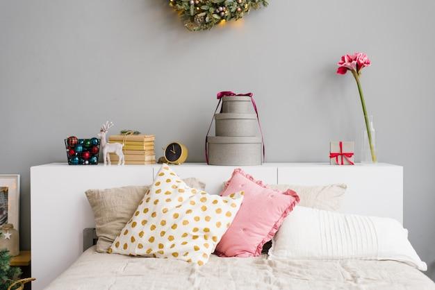 Letto con cuscini bianchi e rosa, decorato per natale e capodanno
