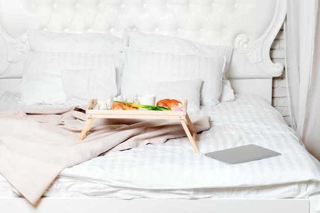 Letto con laptop e colazione, libero professionista o blogger a casa. lavora su computer da casa, mattina e ora di colazione