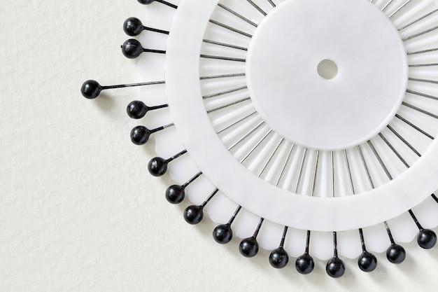 Letto dell'ago bianco con perni neri su sfondo bianco. set di spille da cucito con teste nere. primo piano, fuoco selettivo, vista dall'alto