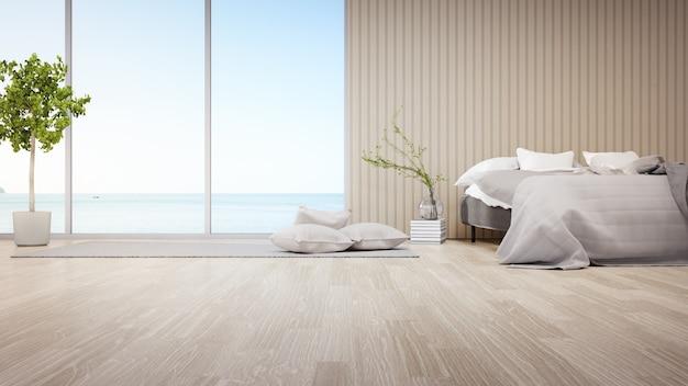 Letto sul pavimento in parquet della luminosa camera da letto contro la testiera in legno nella moderna casa sulla spiaggia o hotel di lusso.