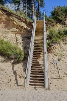 Lettonia. mare baltico. jurkalne. scala verso la ripida sponda delle dune. dune di sabbia con alberi di pino.