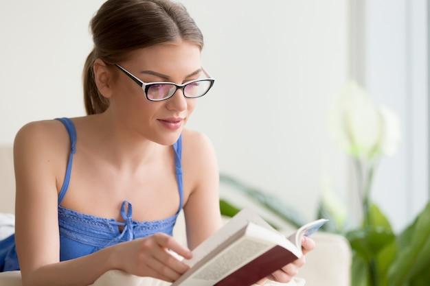 Lettore femminile che gode del libro mentre trovandosi sul sofà