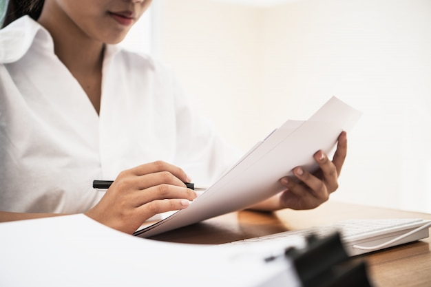 Lettura asiatica della giovane donna di affari o studente universitario