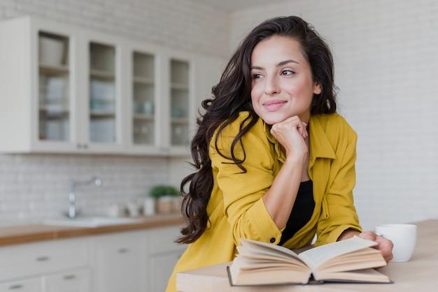 Lettura della donna di smiley del colpo medio nella cucina