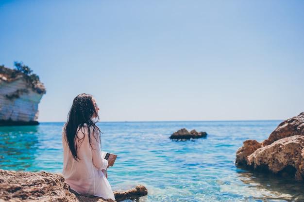 Lettura della giovane donna sulla spiaggia bianca tropicale
