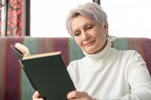 Lettura femminile dell'anziano di angolo basso