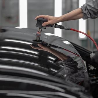 Levigare la parte verniciata dell'auto con uno strumento pneumatico