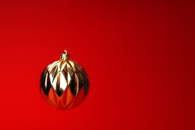 Levitando nella bagattella di natale dell'aria sopra fondo rosso. biglietto natalizio