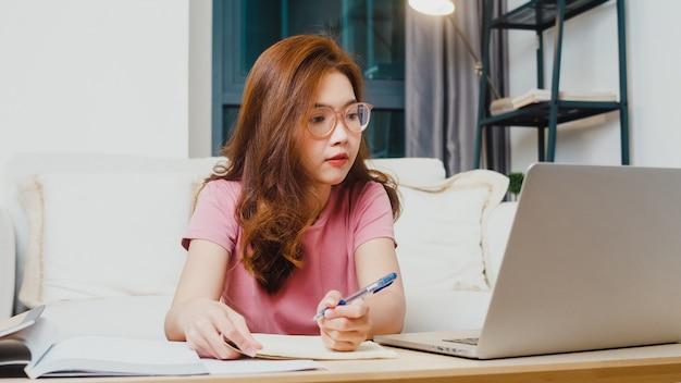Lezione di apprendimento a distanza per studenti giovani asiatici ragazza adolescente con insegnante in linea e studio sul computer portatile in salotto da casa durante la notte. distanziamento sociale, quarantena per la prevenzione del coronavirus.