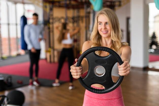 Lezione di fitness giovane donna con pesi