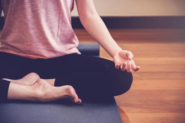 Lezione di pratica di yoga della giovane donna in buona salute, posa del loto con l'istruttore in studio domestico
