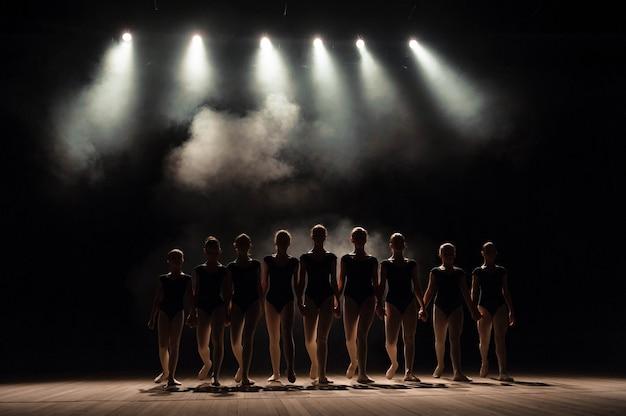 Lezioni di danza classica sul palcoscenico del teatro con luci e fumo. i bambini sono impegnati in esercizi classici sul palco.