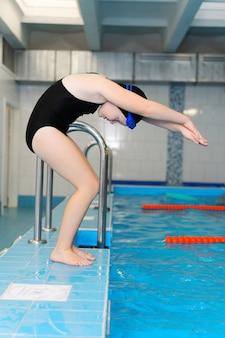 Lezioni di nuoto per bambini in piscina - una bella ragazza dalla pelle chiara nuota nell'acqua