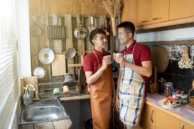 Lgbt l'omosessuale maschile sta aiutando a cucinare il cibo in cucina.