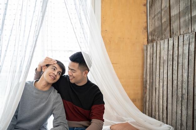 Lgbt men home life: coppia omosessuale maschile abbracciata nel letto della camera da letto