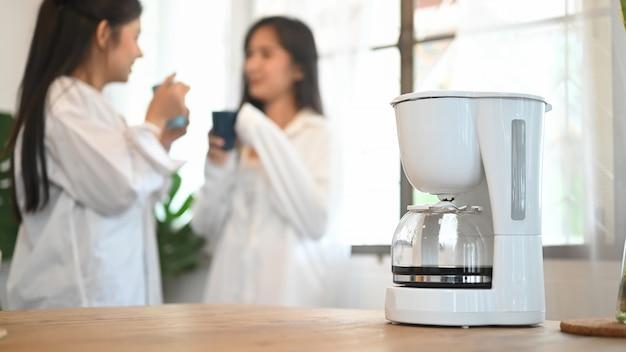 Lgbt sta bevendo caffè e parlando insieme, messa a fuoco selettiva sulla macchina per il caffè.