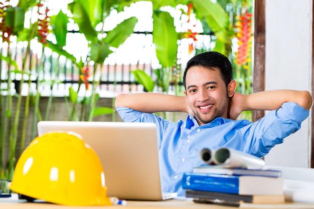 Libero professionista - architetto che lavora a casa su un disegno o una bozza, sulla sua scrivania ci sono libri, un computer portatile e un casco o un elmetto