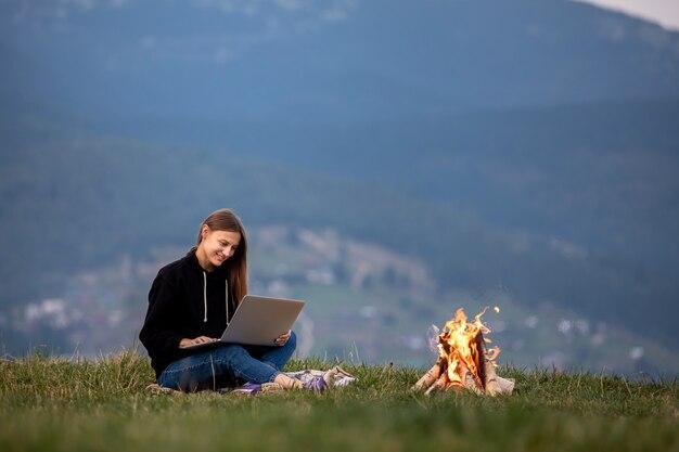 Libero professionista della giovane donna con il computer portatile nelle montagne la sera,