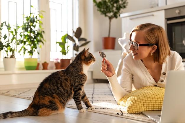 Libero professionista donna giace sul tappeto in salotto, gioca con il gatto un topo giocattolo a casa, lavorando sul portatile