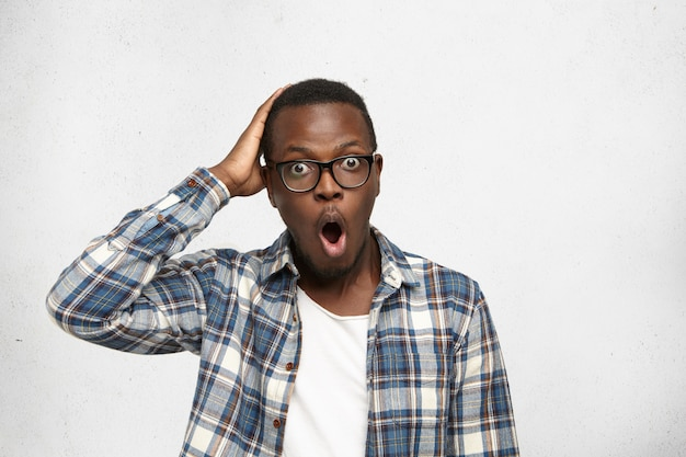 Libero professionista maschio afroamericano dagli occhi da bug in camicia con espressione del viso smemorato che tocca la testa con la mano, rendendosi conto che oggi è la scadenza del suo progetto, aprendo la bocca come se dicesse no!