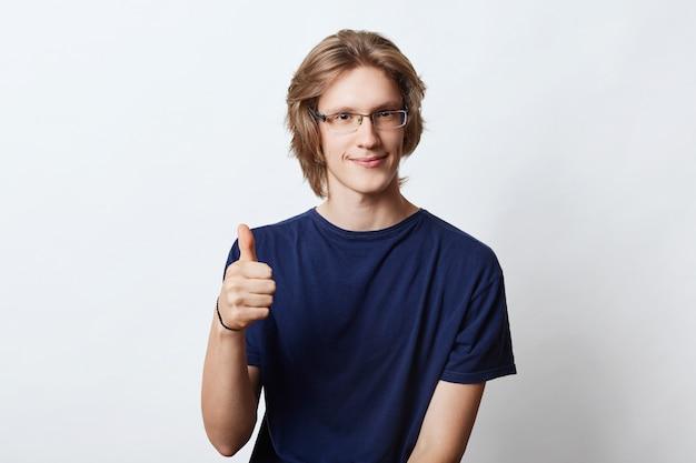 Libero professionista maschio fiducioso con una pettinatura alla moda, con gli occhiali, che mostra il segno giusto mentre alza il pollice, concordando con qualcosa. giovane responsabile che posa sul bianco. concetto di carriera