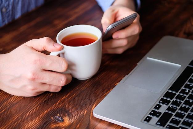 Libero professionista si rilassa bevendo tè e navigando sui social network attraverso il telefono accanto al suo laptop.