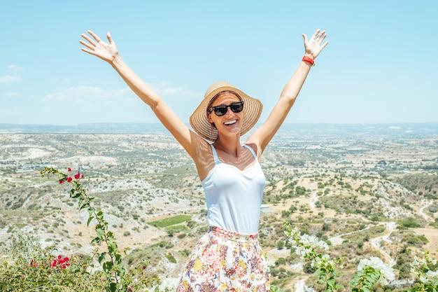 Libertà donna viaggiatore sorridente felice in piedi con le braccia alzate con vista sulla valle. vittoria e concetto di libertà