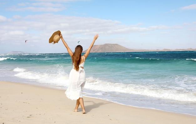 Libertà ragazza felice godendo il vento con le braccia alzate e persone kitesurfering, corralejo dunes beach, fuerteventura, isole canarie