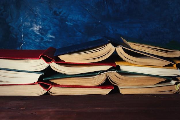 Libri aperti accatastati l'uno sull'altro sul tavolo di legno e sul muro blu scuro