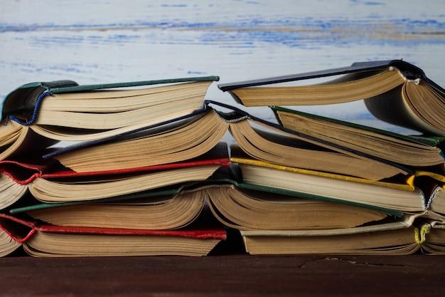 Libri aperti impilati uno sull'altro sulla parete di legno bianca