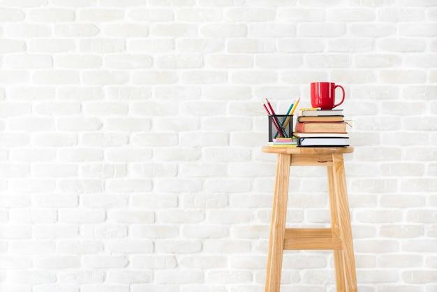 Libri, articoli di cancelleria e tazza di caffè sulle feci di legno in muro di mattoni bianco