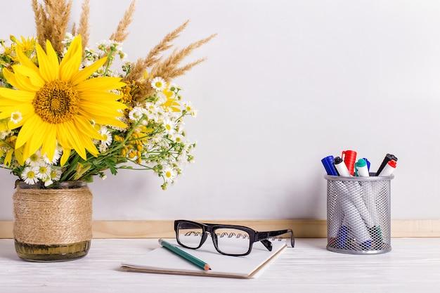 Libri, bicchieri, pennarelli e un mazzo di fiori in un vaso su bianco