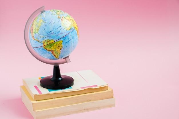 Libri con il modello del globo sul rosa