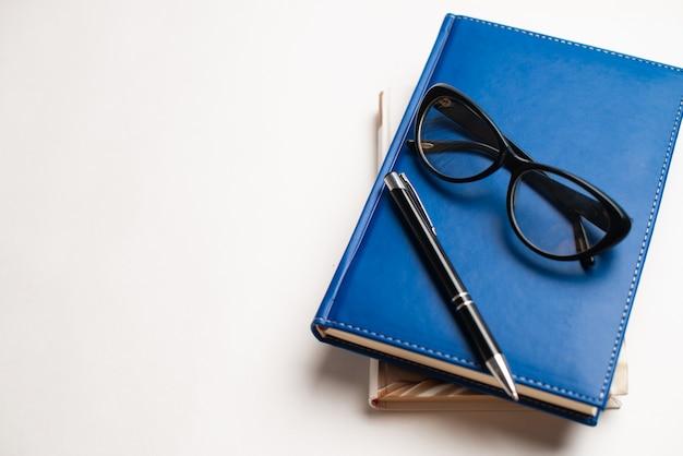 Libri con occhiali e penna