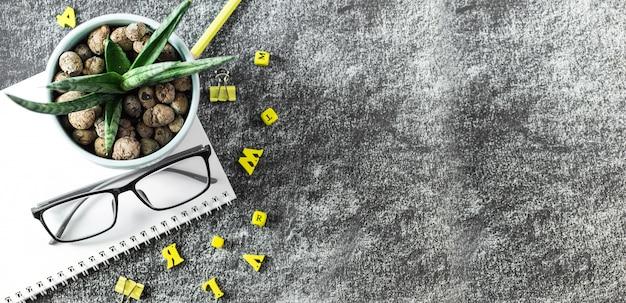 Libri dell'insegnante di occhiali, lettere di legno e un vaso di piante grasse sul tavolo, sullo sfondo di una lavagna con il gesso. il concetto del giorno dell'insegnante. copia spazio.