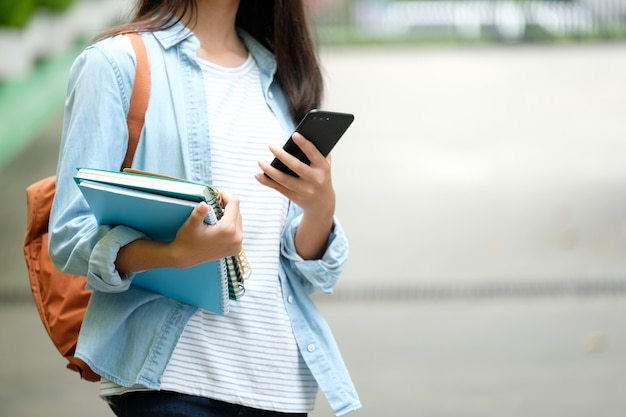 Libri della tenuta della ragazza dello studente e smartphone usando, istruzione online, comunicazione di tecnologia