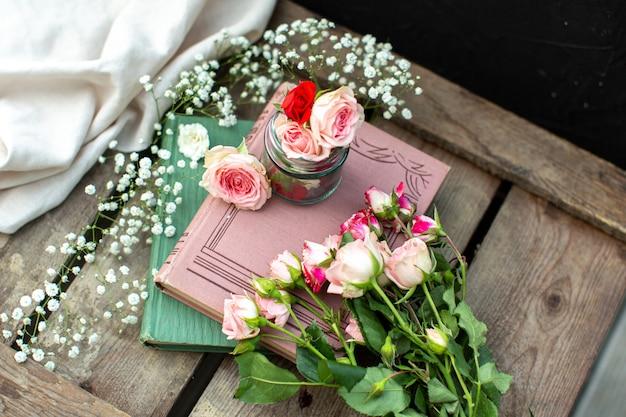 Libri di rose di una vista frontale colorati sul pavimento di legno marrone